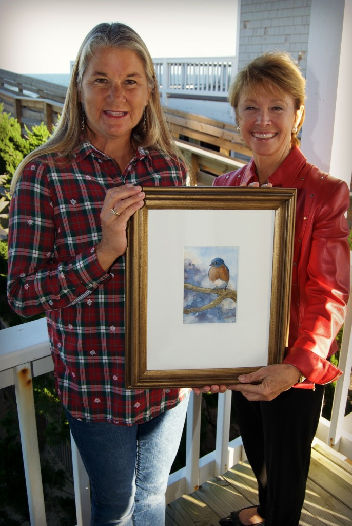 """Holly Robinson, N.E.S.T. Board member (right) presents Kim Stoltz, as the proud winner of the 2015 art raffle """"Between Heaven and Earth"""" by E.M. Corsa."""